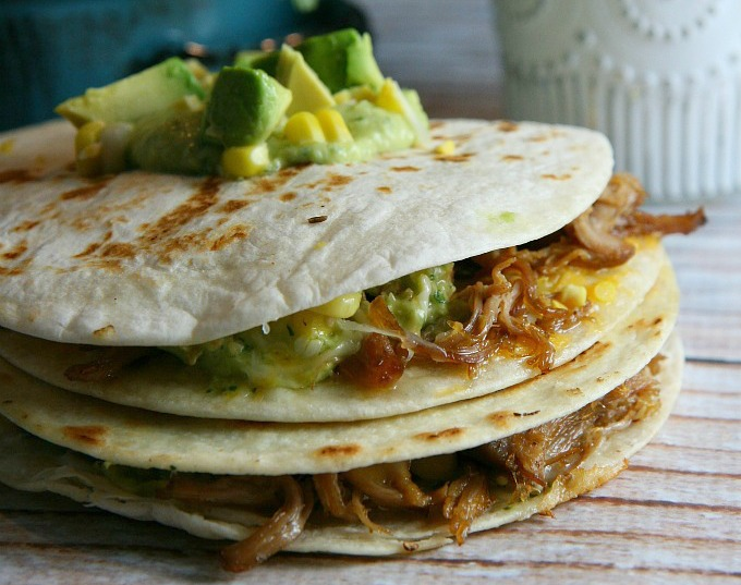Pulled Pork Quesadillas...pulled pork, sweet corn, and melted cheese layered between flour tortillas, and topped with a tangy tomatillo guacamole...a delicious alternative for Mexican night!