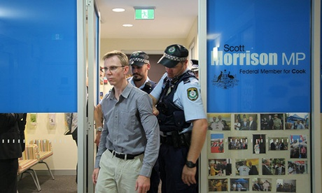 Justin Whelan is led by police after taking part in a prayer vigil at Scott Morrison's office. Photograph: Kate Ausburn
