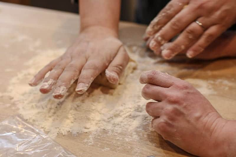 As the dough begins to mix and form, begin pressing it down and folding it with the heal of your hand.