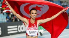 Habiba Ghribi of Tunisia holds her national flag after placing second in the women's 3,000 metres steeplechase final at the IAAF World Athletics Championships in Daegu August 30, 2011.   REUTERS/Phil Noble (SOUTH KOREA  - Tags: SPORT ATHLETICS)