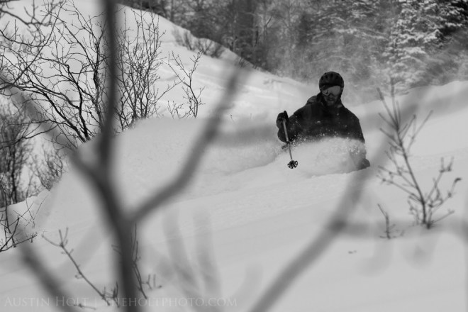 A photograph of a telemark skier making a turn in deep powder snow in Utah.