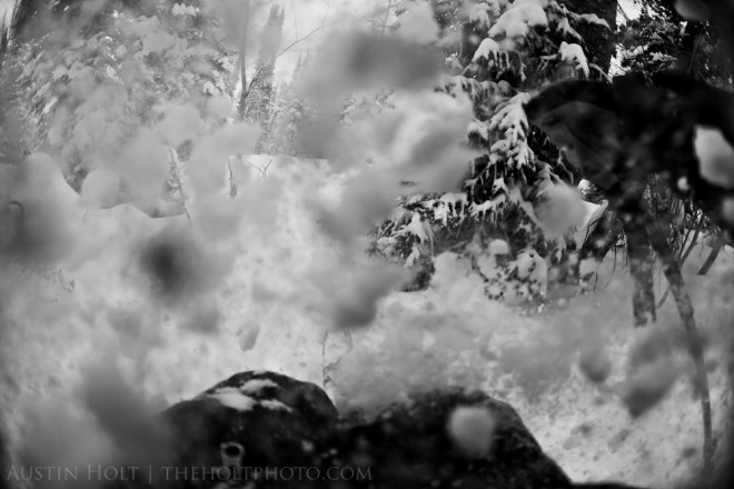 Chunks of snow fly in the air as I ski through deep powder in Utah