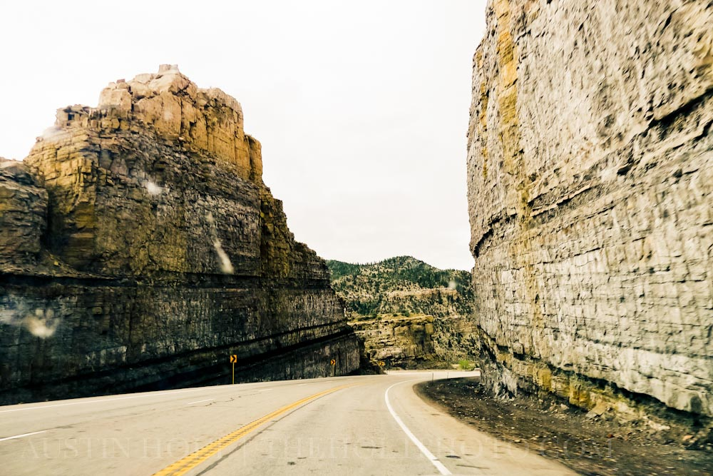 Rock walls stand tall along the side of the highway in Utah.