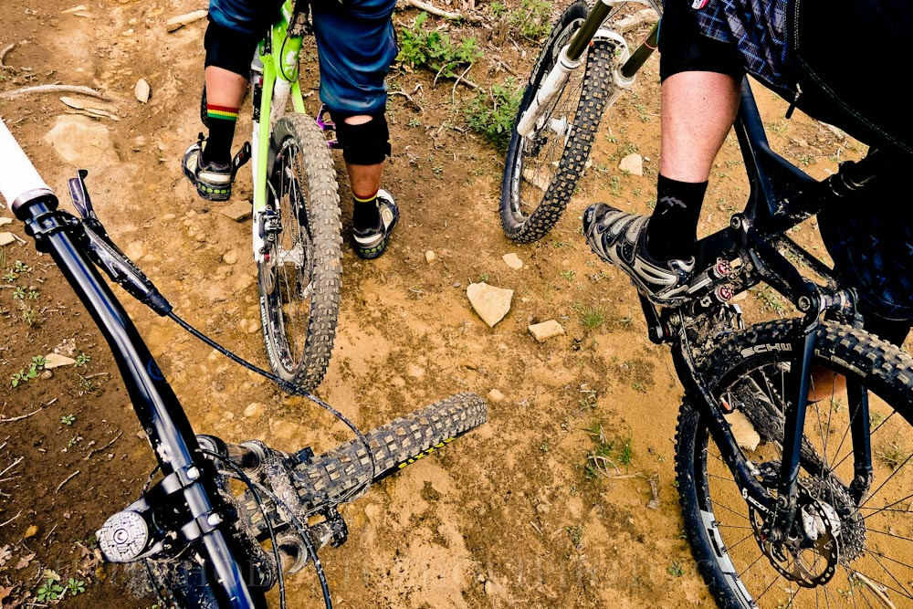 Looking down at the trail below the bikes, shoes, and muddy tires of three mountain bikers in Utah.
