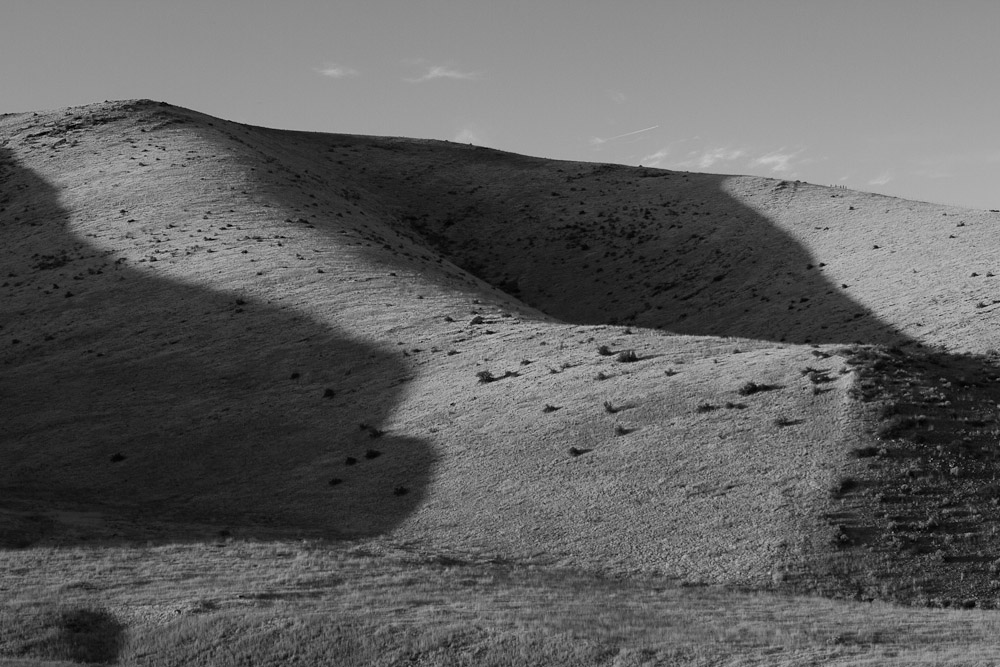 Faint shadows stretch over low, rolling hills in Utah.