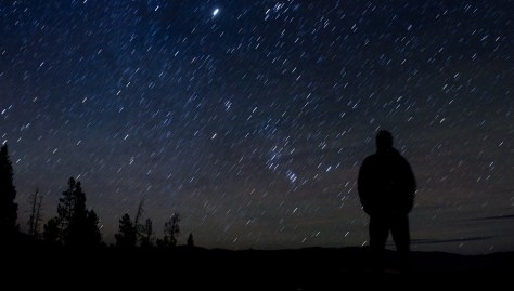 A silhouette of a star gazer watching the starry, night sky over Stanley, Idaho.