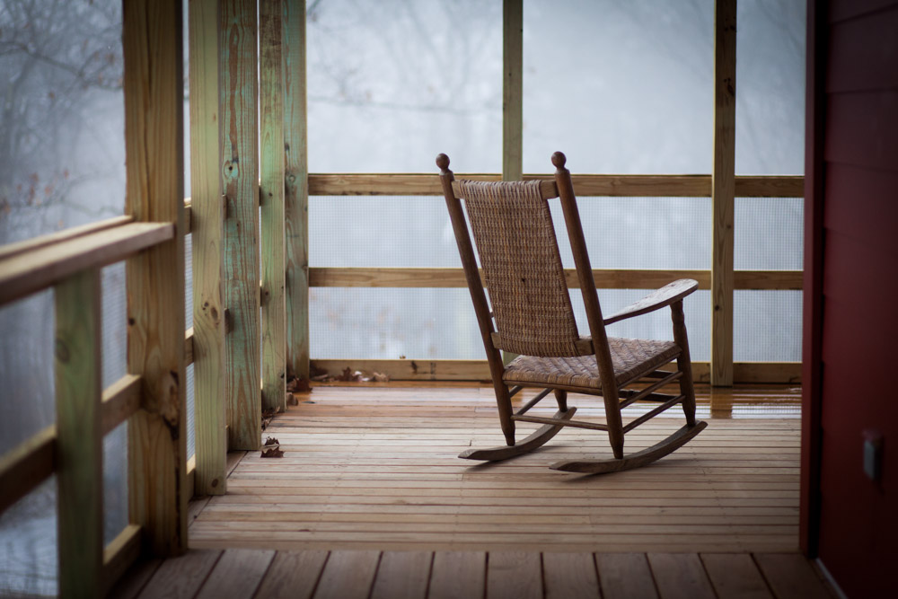 A rocking chair sits empty on the porch.