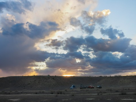 A brilliant sunset bursting through the clouds over a tent in Fruita, Colorado
