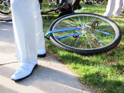 The powder blue dress shoes of a unicyclist. His unicycle lays on the grass beside his feet.