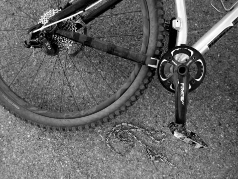 A Diamondback Mason 29er hardtail mountain bike lies on its side and beside it a broken chain on the pavement.