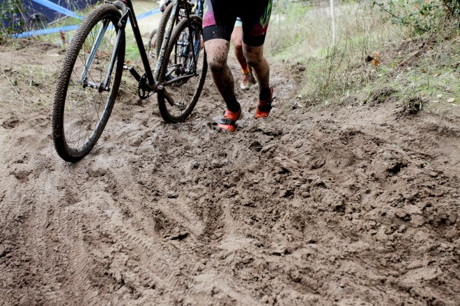 A cyclocross racer digs in up a muddy hill already packed with footprints.