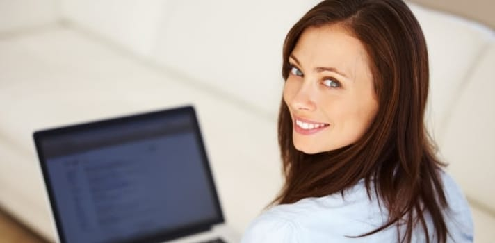 Portrait of beautiful business woman using laptop while looking at you