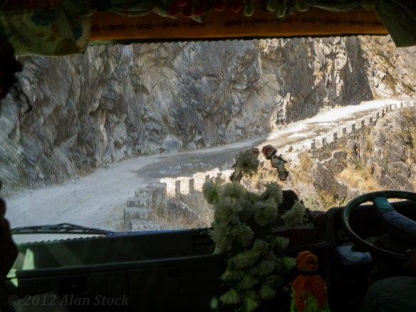 A rare bit of road with barriers, a death plunge is below. As usual, the Nepali bus cabin is filled with decorations and Hindu images