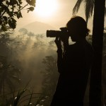 Silhouette photographer at misty sunrise in Bali jungle sun rays volcano in distance