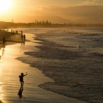 Silhouette child dancing on beach sunset Byron Bay Australia happy
