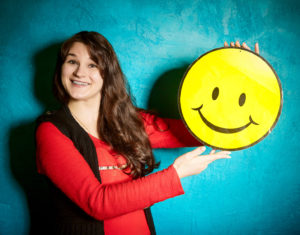 young woman holding a big yellow smiley