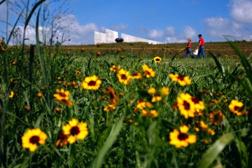 Visitors to the Flight 93 National Memorial walk up a path to the newly dedicated Flight 93 National Memorial Visitors Center, rear, in Shanksville, Pa, Friday, Sept. 11, 2015. Hundreds of victims' relatives gathered for what has become a tradition of tolling bells, moments of silence and the reading of the names of the nearly 3,000 people killed in the terror strikes at the World Trade Center, the Pentagon and a field near Shanksville, Pennsylvania. (AP Photo/Gene J. Puskar)