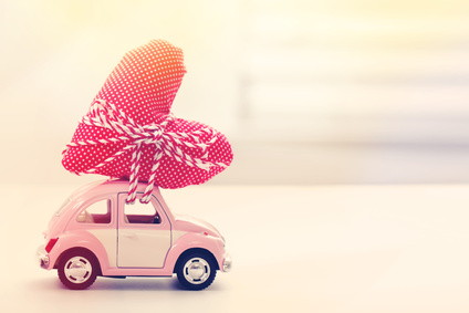 Miniature car carrying a red heart cushion