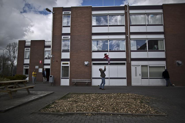 In this Friday, April 8, 2016 photo, a migrant plays with a girl at the former prison of Westlingen in Heerhugowaard northwestern Netherlands. The Dutch government has let Belgium and Norway put prisoners in its empty cells and now, amid the huge flow of migrants into Europe, several Dutch prisons have been temporarily pressed into service as asylum seeker centers. (AP Photo/Muhammed Muheisen)