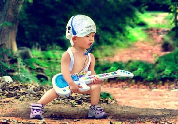 طفل يعزف الموسيقي علي الة الجيتار