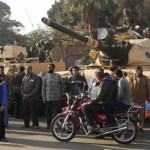 Supporters of the Muslim Brotherhood stand near tanks that were just deployed outside the Egyptian presidential palace in Cairo