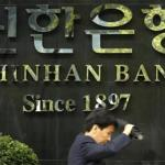 A pedestrian walks past a branch office of Shinhan Bank in central Seoul