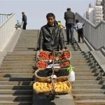 A street vendor pushes his mobile fruit stall on a pedestrian overpass in Beijing