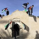 Palestinian and foreign activists hold Palestinian flags as they climb on top of a structure in an old village in the Jordan Valley near Jericho