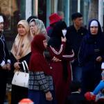 Uighur women stand next to a street to wait for a bus in downtown Urumqi