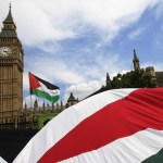 Demonstrators carry Palestinian flags as they protest outside the Houses of Parliament in central London