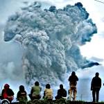 Indonesian men watch Mount Sinabung spewing volcanic materials d