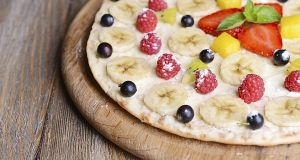 Sweet pizza with fruits on table close-up