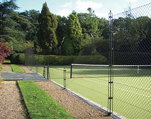 Tennis Court Construction - Mature trees and an obelisk fence surround an AMSS tennis court