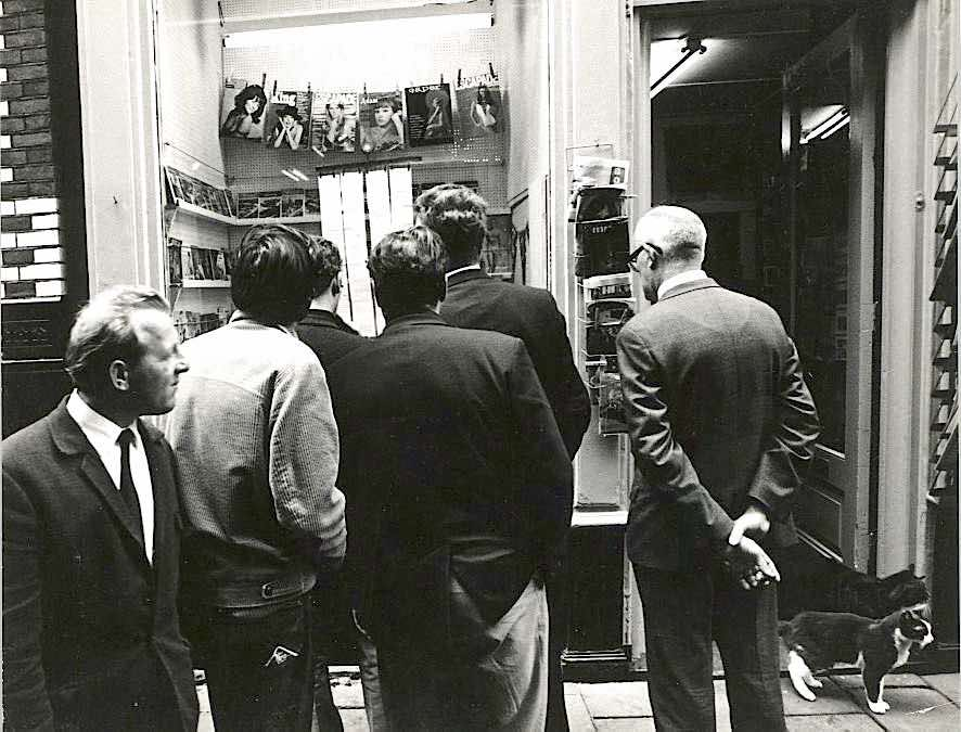 The Red Light District of Amsterdam in 1969. Some men watch erotic magazines in a sex shop.