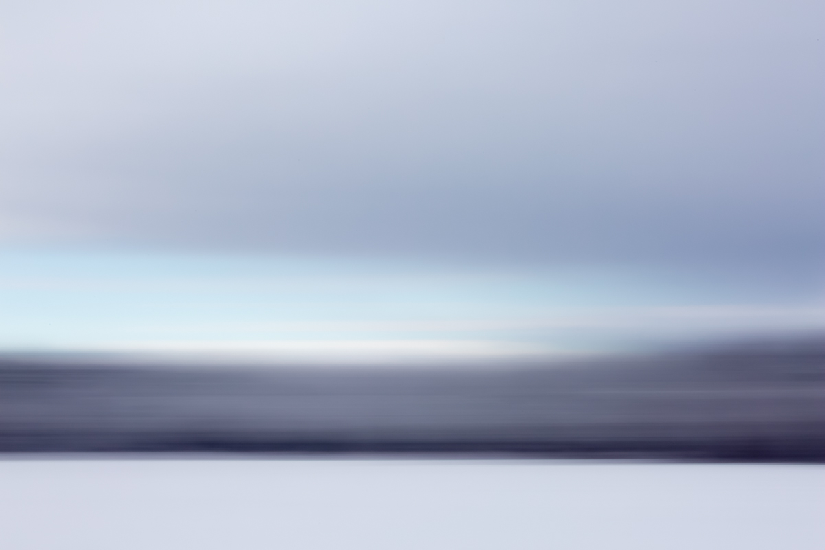 Photographic abstract image of a snowy field with trees and a grey sky.