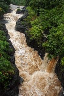 Коричневый поток в узком ущелье после тропического ливня.
