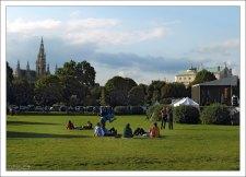 Местные и туристы отдыхают на лужайке перед дворцом Hoffburg.