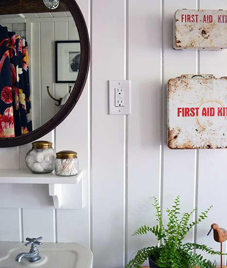 White planked walls in this old farmhouse bathroom renovation with vintage accessories including a flea market mirror, salvage cast iron sink, and old metal first aid kits.