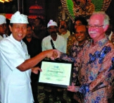 Bali governor Made Mangku Pastika accepts an award from FAO representative James McGrane. (FAO photo)
