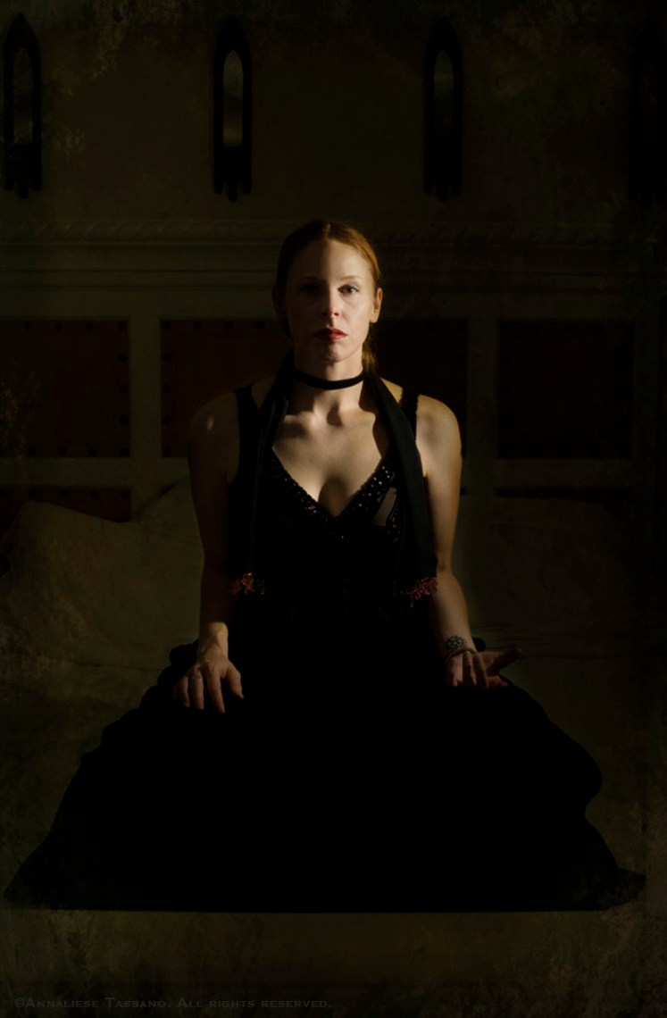 A white woman with red hair and lipstick wearing a black dress and choker sits crossed legs in a dark, wainscoted room, her left hand in a mudra.