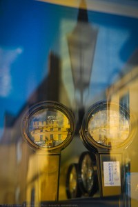 Reflections of blue skies and stone buildings, and magnifying lenses in the window of a Dublin, Ireland optical shop.