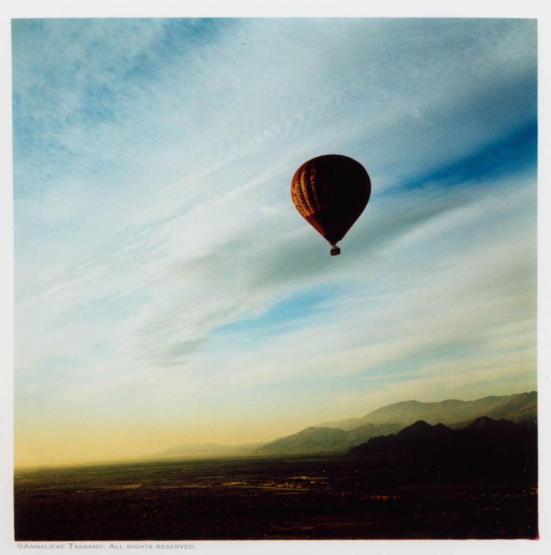 A cross process image of a balloon floating voer the desert valley of Palm Springs, California.
