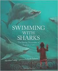 A girl pressed against an aquarium tank watches sharks swim