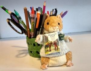 Stuffed library hamster holds a tiny copy of Mountain Chef.