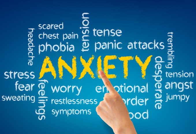 Hand pointing at a Anxiety word illustration on blue background.