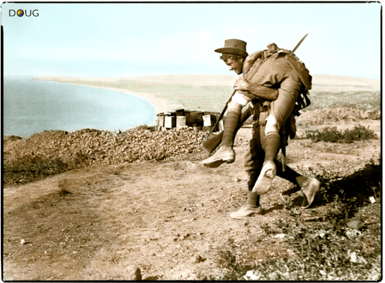 An Australian carrying his wounded mate to a medical aid post for treatment near Suvla on the Aegean coast of Gallipoli peninsula in the Ottoman Empire, 1915. The view is looking north-west from Walker's Ridge towards the Suvla Plain