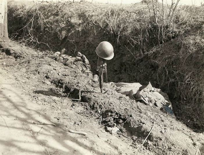 Helmet and Rifle mark the spot in a ditch by road where two Infantrymen gave their lives, during a new drive by Seventh Army which opened on a front of fifty miles from Saarbrücken to the Rhine.