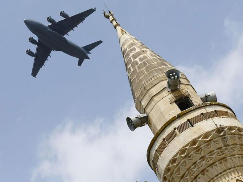 A US Air Force Boeing C-17A Globemaster III large transport aircraft flies over a minaret after taking off from Incirlik air base in Adana, Turkey, on 12 August 2015 Reuters