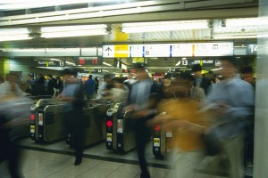 People walking through automatic ticket wicket at station, blurred motion, Tokyo, Japan