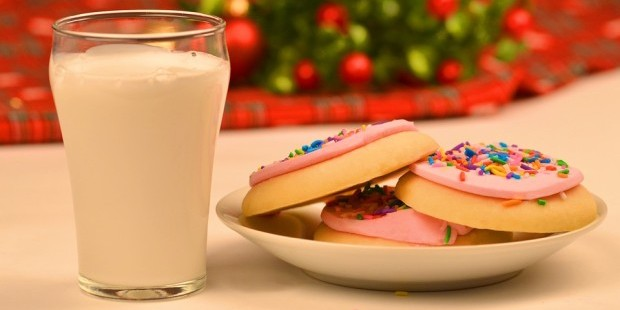 dietary guidelines: Dairy is still a part of USDA food guidelines. Glass of milk and cookies with pink frosting and sprinkles.